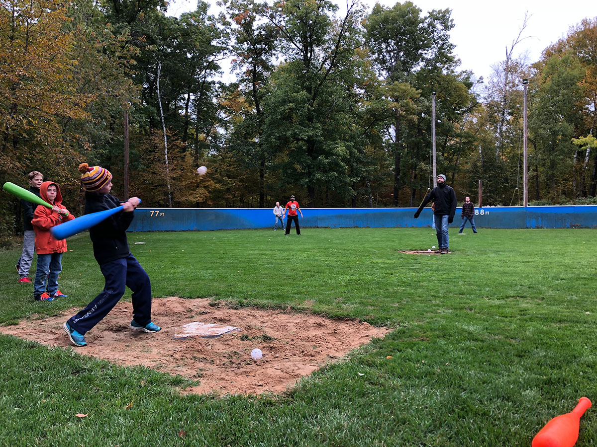 Kids and adults playing wiffleball